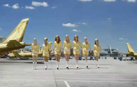 Mostesses walk on the tarmac by a Lynx Jet plane