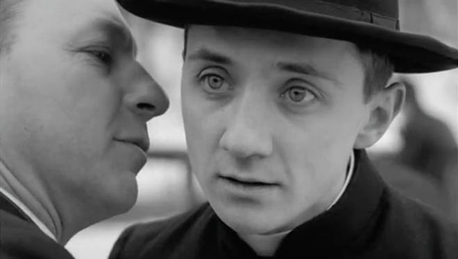 Priest whispers in the ear of a junior priest in Stella Artois TV Ad