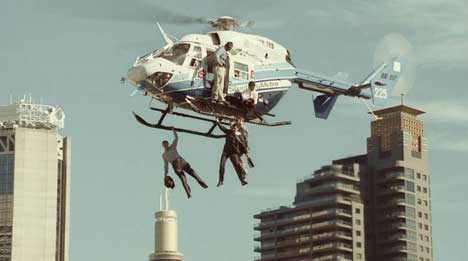 Men suspended from a helicopter over Stunt City