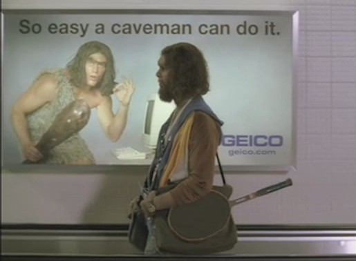Caveman stops to look at poster in airport