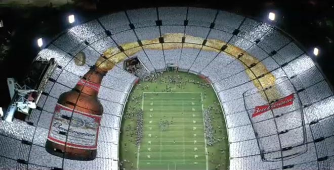 Football players watch as human glass fills with Budweiser beer