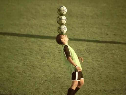 Brazilian football player balances three balls