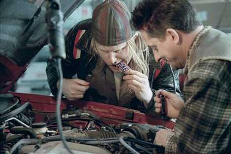 Mechanics lean over an engine before sharing a Snickers bar