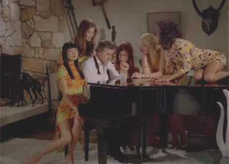 Bruce Campbell surrounded by women at the piano