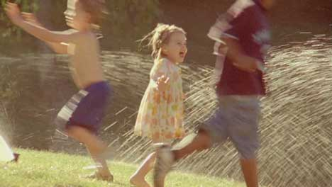Girl runs through water sprinkler in Heinz Pourable Sunshine picnic
