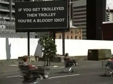 Trolley riders speed past sign in Progressive Enterprises TV ad