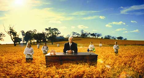 Sam Kekovich by a wheat field with choir boys and girls