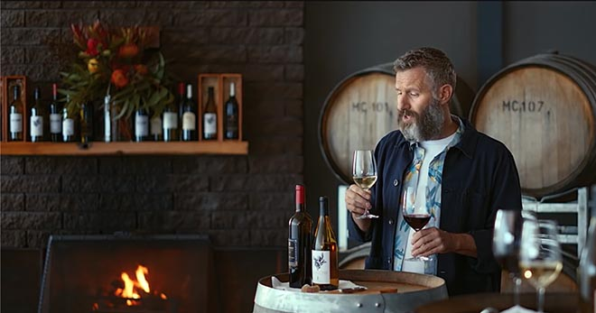 Adam Hills with wine in Tourism Australia Matesong