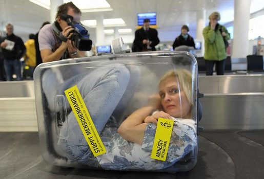 Frau im Koffer in Amnesty International stunt at Munich airport