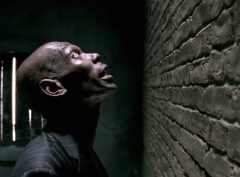 Maxi Jazz sings looking up at brick wall in Faithless Mass Destruction music video