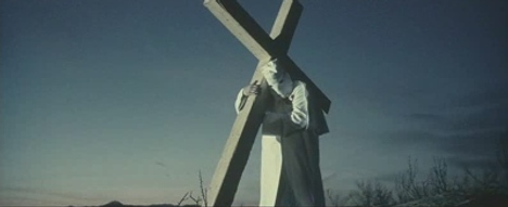 Klu Klux Klan member carries white cross