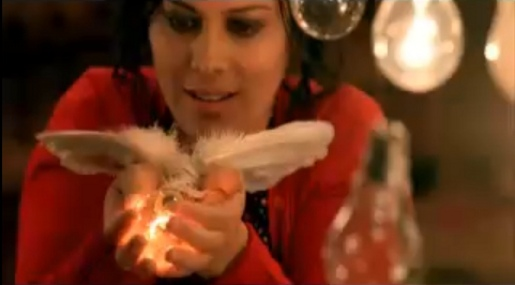 Anika holds lightbulb with wings in Deams in My Head music video