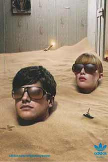 A man and a woman buried in the sand are saved from glare in Adidas Originals print ad