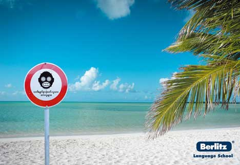 Beach warning sign in Berlitz print advertisement