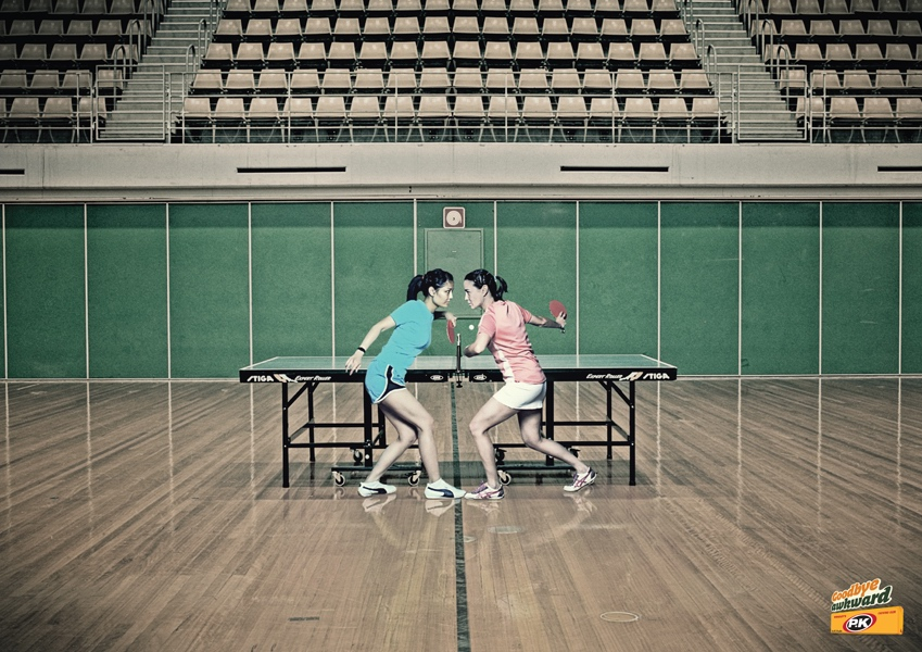 Ping pong players stand close in PK Gum print ad