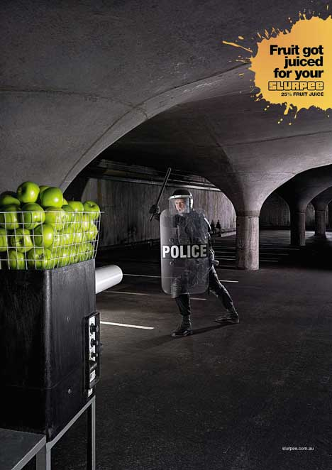 Policeman in riot gear faces tennis practice machine