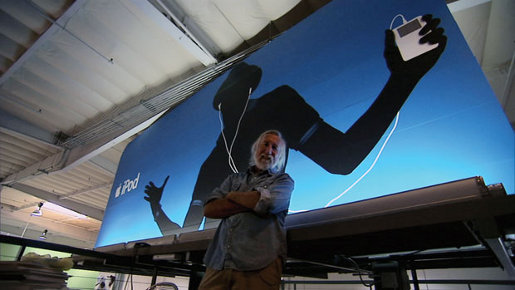 Lee Clow in front of an iPod billboard